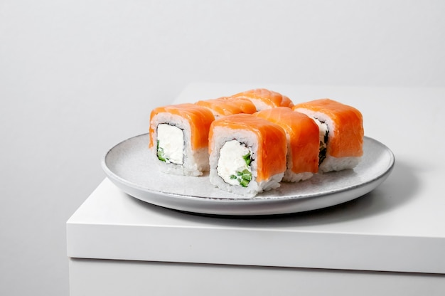 Involtini di philadelphia con salmone, cetriolo e formaggio su piatto su sfondo bianco