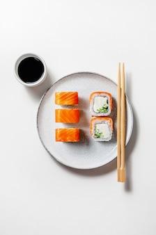 Involtini di philadelphia con salmone, cetriolo e formaggio su piatto con salsa di soia su sfondo bianco