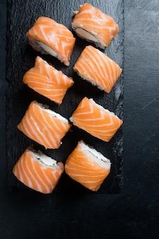 Rotoli di sushi di salmone di filadelfia su sfondo scuro. cucina giapponese e concetto di cibo asiatico