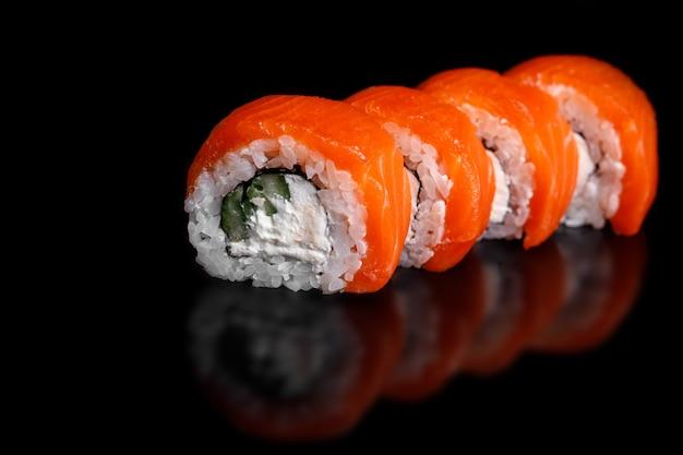 Philadelphia sushi roll su una superficie nera con la riflessione.