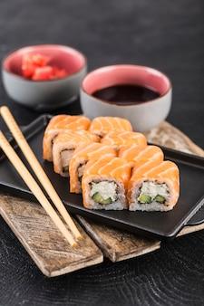 Rotolo di sushi philadelphia con salmone, cetriolo, avocado e crema di formaggio su una superficie scura