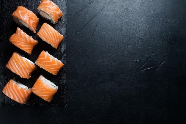 Rotoli di sushi di philadelphia su sfondo scuro. arte della fotografia di cibo. concetto di spazio libero