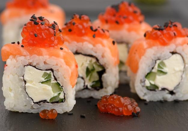 Sushi di filadelfia con caviale rosso su una tavola di ardesia nera, si chiuda