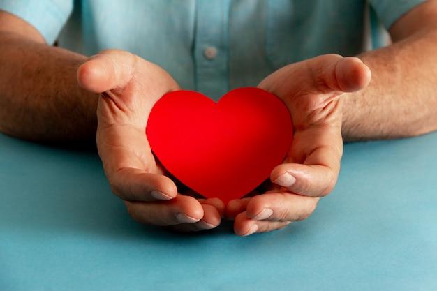 Filantropia e concetto di beneficenza. mani che offrono un cuore di carta. messa a fuoco selettiva.