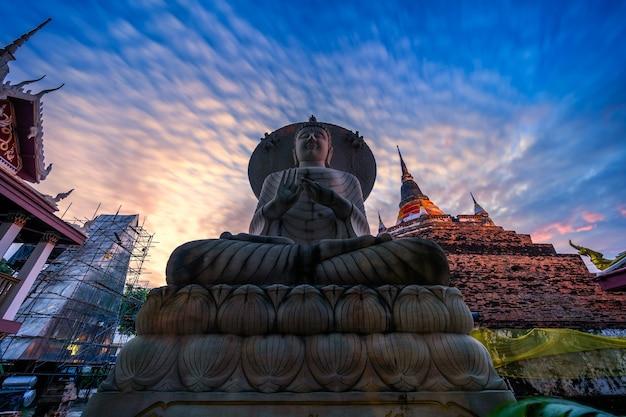 Phitsanulok, thailandia - 10 ottobre 2020: la statua del buddha e phra chedi luang nel tempio (lingua tailandese: wat ratchaburana) è un tempio buddista è una grande attrazione turistica a phitsanulok, in thailandia.