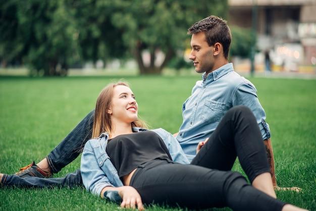 Persone dipendenti da telefono, uomo e donna si trovano sull'erba nel parco estivo e utilizzano i loro smartphone, social addict