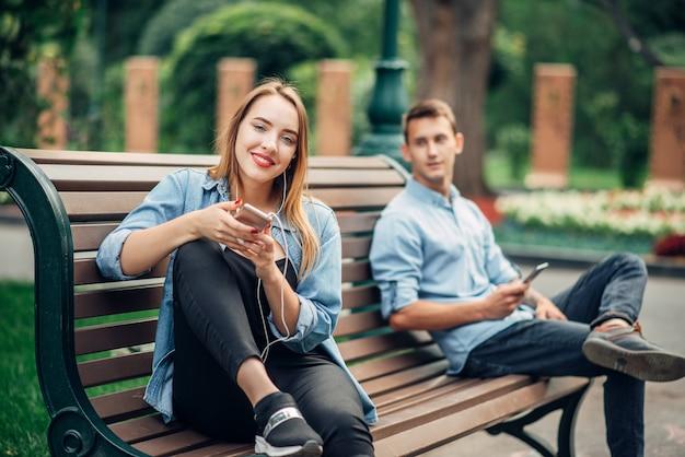 Dipendenza dal telefono, coppia che si ignora a vicenda sulla panchina nel parco. uomo e donna che usano i loro smartphone, persone dipendenti dai social