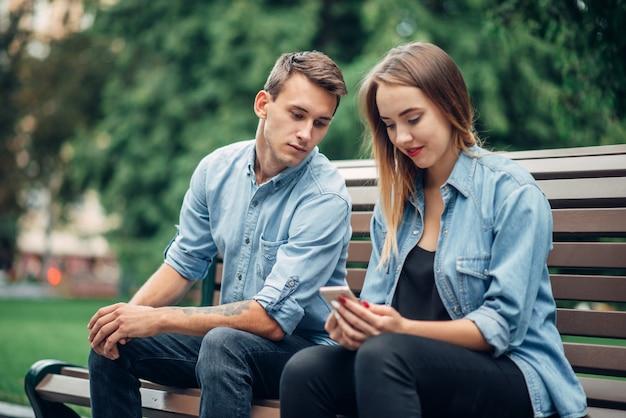 Dipendenza da telefono, giovane coppia in panchina nel parco