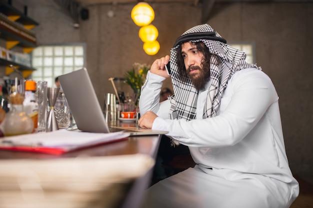 Al telefono uomo d'affari arabo che lavora nel centro business dell'ufficio utilizzando gadget del dispositivo