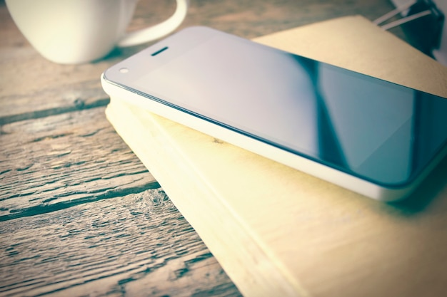 Telefono sul libro e caffè sul tavolo di legno