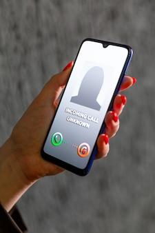 Telefonata da numero sconosciuto. scam, frode o phishing con il concetto di smartphone. chiamante scherzo, truffatore o sconosciuto. donna che risponde alla chiamata in arrivo. persona falsa con identità falsa.