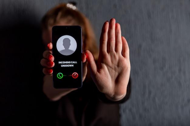 Telefonata da numero sconosciuto. truffa, frode o phishing con il concetto di smartphone. chiamante scherzo, truffatore o sconosciuto. donna che risponde alla chiamata in arrivo. persona falsa con identità falsa.