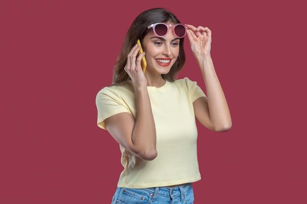 Telefonata. bella giovane donna sorridente con trucco che toglie gli occhiali da sole parlando sullo smartphone