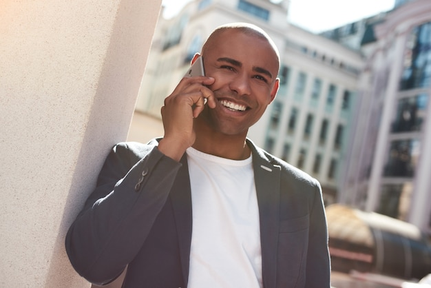 Telefonata giovane uomo in piedi sulla strada della città che parla con un amico sullo smartphone sorridente