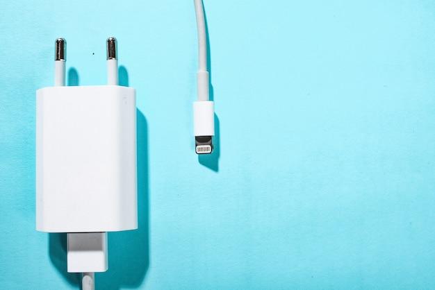 Caricatore del telefono su sfondo blu con copia spazio