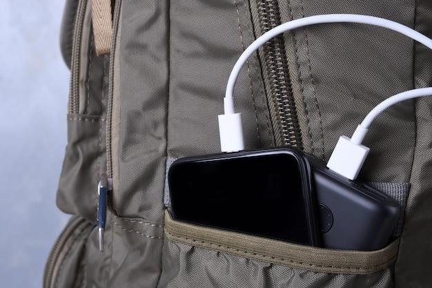 Ricarica del telefono, powerbank carica smartphone, cellulare con banca di energia. profondità di campo sulla power bank nella borsa dello zaino