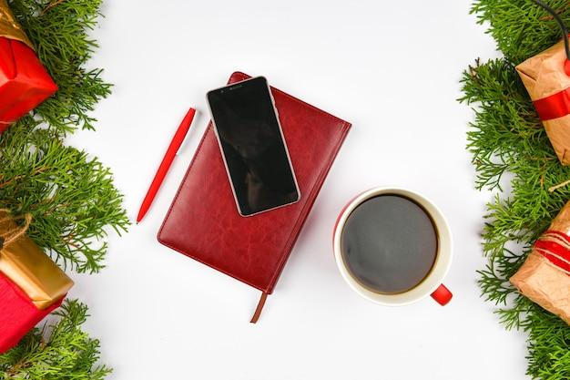 Telefono, tazza da caffè sullo spazio di natale. vista dall'alto. posto per scrivere. spazio bianco. accogliente riposo. tazza di latte, taccuino, penna, telefono, confezione regalo. aghi.