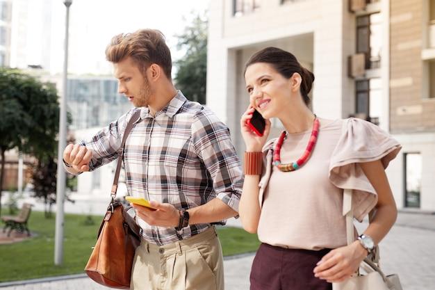 Conversazione telefonica. bella giovane donna che parla al telefono mentre va con il marito a lavorare