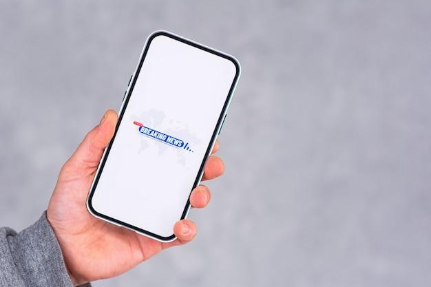 Display del telefono con l'icona ultime notizie su sfondo chiaro. l'uomo tiene in mano uno smartphone mockup.