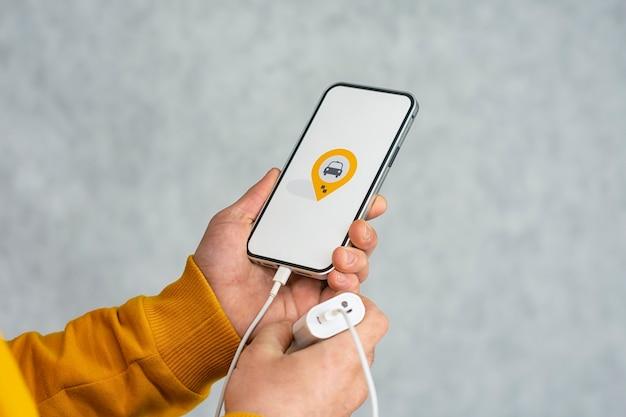 Display del telefono con icona taxi su sfondo chiaro. l'uomo tiene in mano uno smartphone mockup.