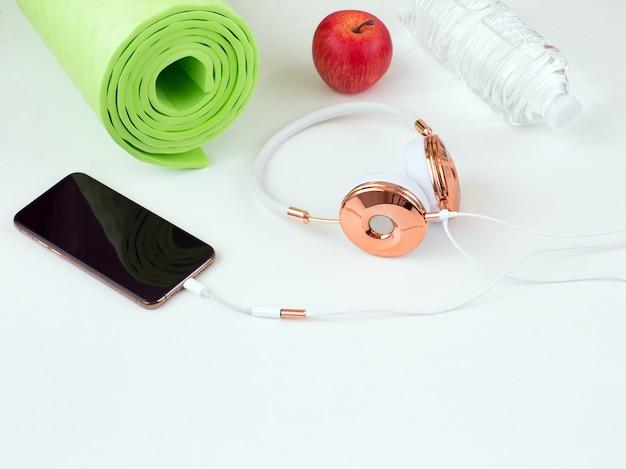 Telefono, auricolari, tappetino yoga, mela e acqua in una bottiglia