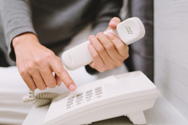 Al telefono a casa: giovane che chiama parlando al telefono mentre giaceva in camera da letto a casa.
