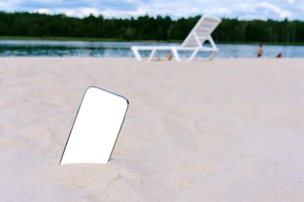Modello del telefono nella sabbia sulla spiaggia. sullo sfondo di un lettino prendisole, acqua e alberi.