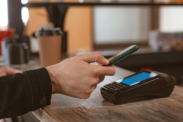 Primo piano del pagamento telefonico di un cliente che collega uno smartphone a un terminale di pagamento per pagare un caffè in un bar