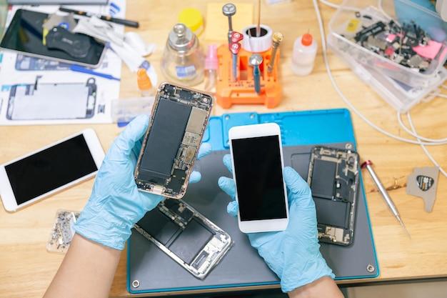 Concetto di riparazione del telefono un riparatore maschio del telefono che indossa guanti e una maschera che controlla i componenti del telefono cellulare.
