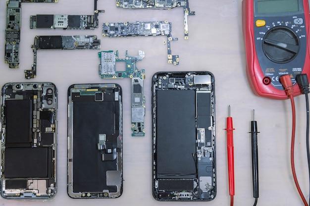 Concetto di riparazione del telefono diversi dispositivi elettronici smontati nei componenti come le coperture, i circuiti stampati, i corpi.