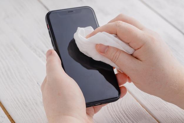 Disinfezione dello schermo del telefono per la pulizia dei panni rimuovendo i germi con salviette antibatteriche per il virus corona covid-19