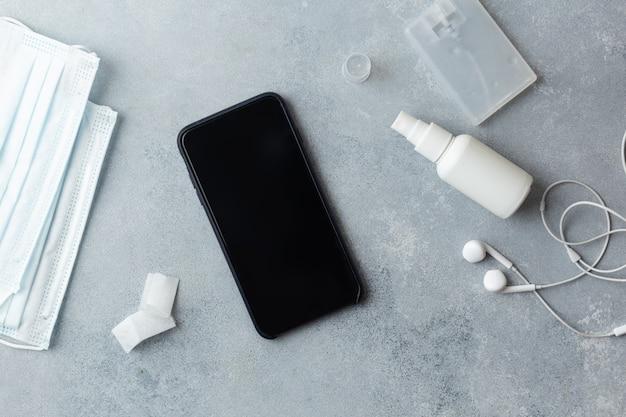 Disinfezione dello schermo del telefono pulire la donna che rimuove i germi con salviette antibatteriche per il virus corona covid-19