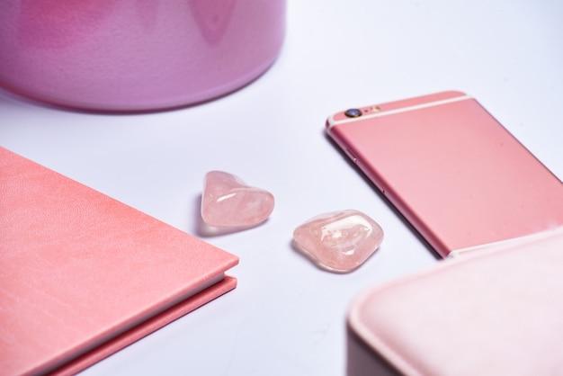 Telefono, vaso, blocco note e bordo della borsa per il trucco in stile rosa.