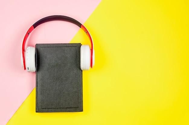 Telefono con auricolari e libro su sfondo di carta colorata. concetto di audiolibro.
