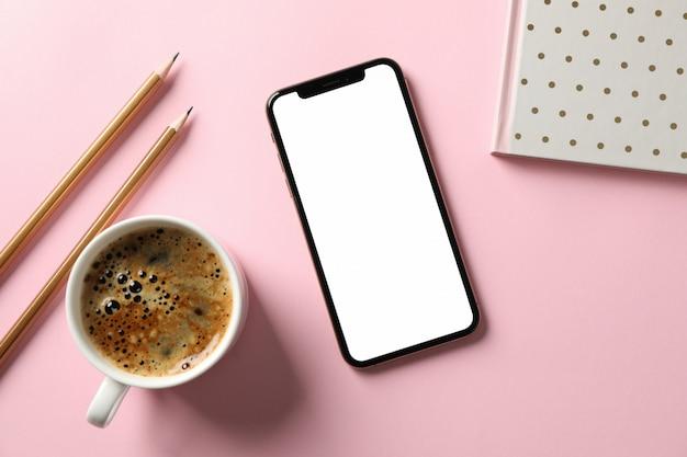 Telefoni con lo schermo, il quaderno, le matite e la tazza di caffè vuoti su fondo rosa, vista superiore
