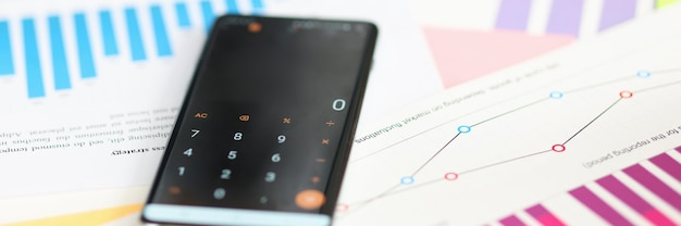 Telefono con la calcolatrice inclusa sdraiata sui documenti nel concetto di crescita del profitto del primo piano dell'ufficio