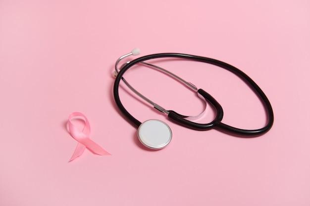 Consapevolezza del fonendoscopio e del nastro rosa satinato, simbolo internazionale del mese di sensibilizzazione sul cancro al seno in ottobre. isolato su sfondo rosa con spazio di copia. assistenza sanitaria e concetto medico delle donne.