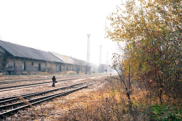 Foto delle rotaie abbandonate e di una stazione ferroviaria