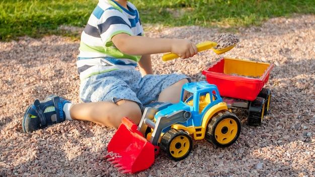 Foto di un bambino adorabile di 3 anni che gioca con la sabbia e tu camion e rimorchio nel parco. bambino che scava e costruisce nella buca di sabbia sand