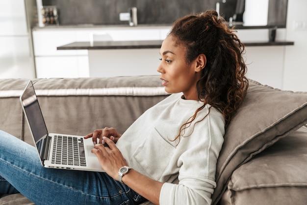 Foto di adorabile donna afroamericana utilizzando laptop, sdraiati sul divano nel luminoso soggiorno