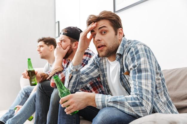 Foto di uomini adulti di 30 anni concentrati e tesi a guardare la partita di calcio a casa, con la birra in mano