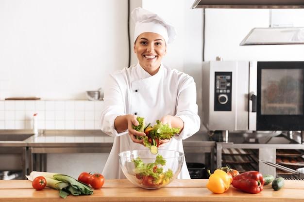 Foto del capo della donna adulta che indossa l'uniforme bianca che produce insalata con verdure fresche, in cucina al ristorante