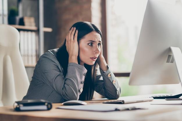 Foto di una ragazza spaventata che lavora a distanza computer remoto pc toccare le mani testa frustrata per la perdita del lavoro crisi del capo notifica covid indossare giacca giacca sedersi tavolo scrivania nella postazione di lavoro