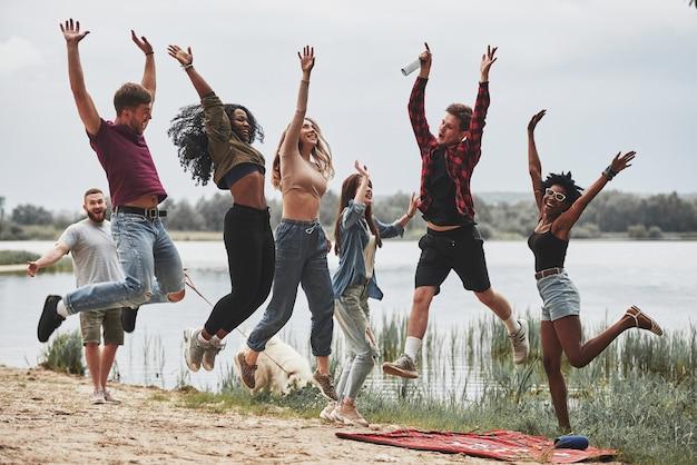 Foto in aria. tutti stanno saltando. un gruppo di persone fa un picnic sulla spiaggia. gli amici si divertono durante il fine settimana.