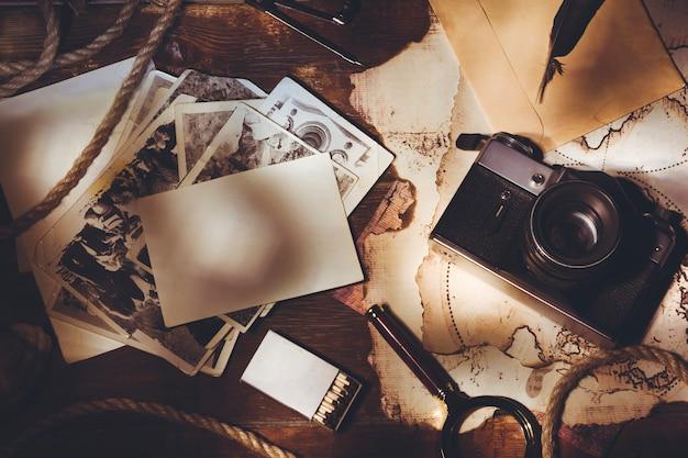 Album fotografico con foto di viaggio e vecchia macchina fotografica vintage su uno sfondo di vecchie mappe