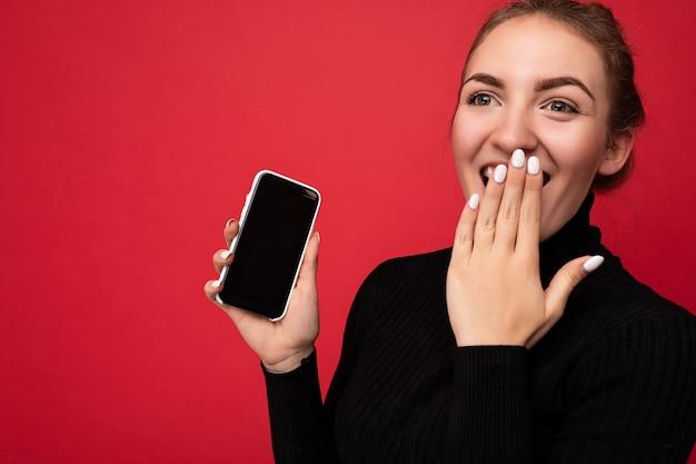 Foto di stupito attraente positivo giovane donna bruna che indossa un maglione nero in piedi isolato sopra la parete rossa che mostra il telefono cellulare con lo schermo vuoto