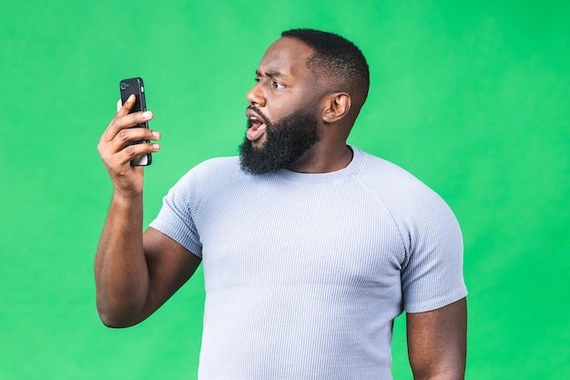 Foto di un uomo afroamericano nero stupito sapendo di essere diventato vincitore di qualcosa di così gioioso godendosi le informazioni sulle notizie mentre era isolato su sfondo verde. utilizzo del telefono cellulare.