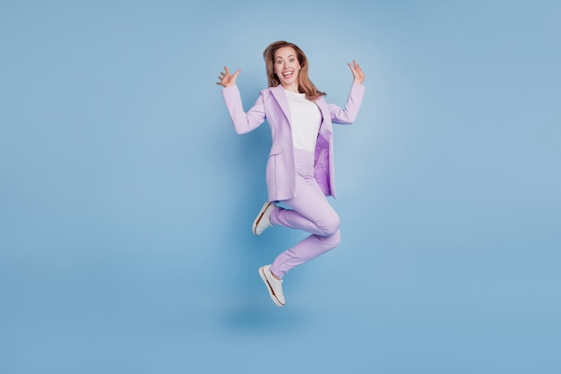 Foto di una donna d'affari stupita che salta su sfondo blu isolato bocca aperta