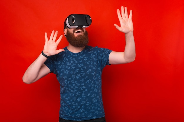 Foto di un uomo barbuto stupito ed eccitato che ha un'esperienza di realtà virtuale con casco vr