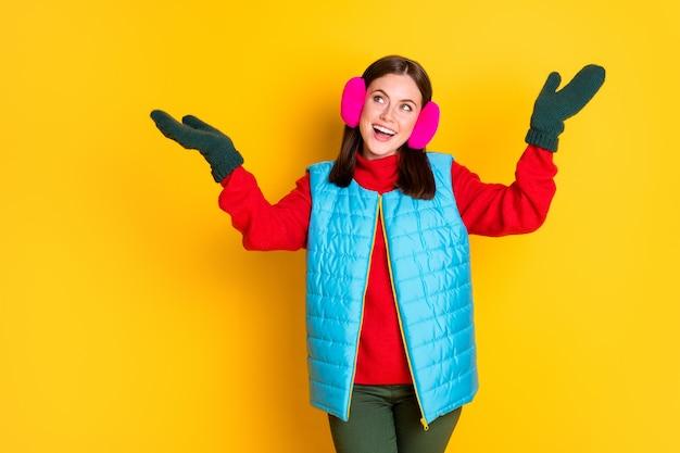 Foto di una ragazza eccitata stupita che tiene la mano cattura aria volare fiocchi di neve copyspace indossa abiti rosa blu stagione isolati su uno sfondo di colore brillante brillante